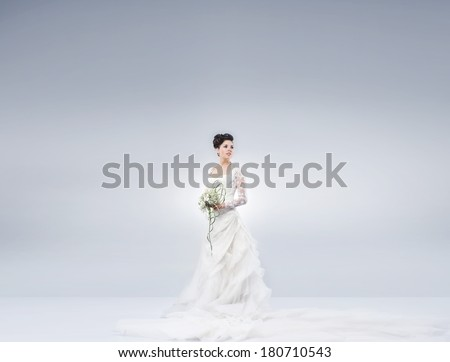 Young and beautiful bride standing with the flower bouquet over the grey background. There is a blank space for any text. - stock photo