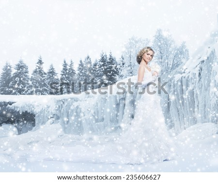 Young and beautiful bride with a flowers walking near the frozen waterfall - stock photo