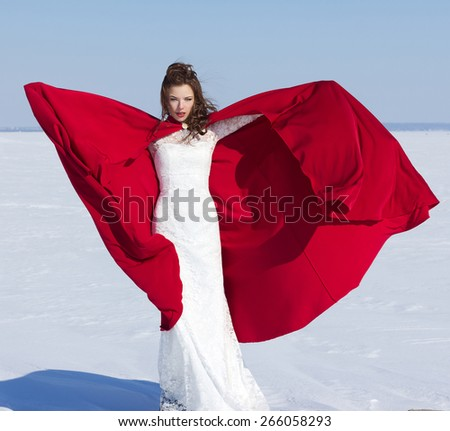 Young and beautiful bride with the red fabric playing with wind in winter background. - stock photo