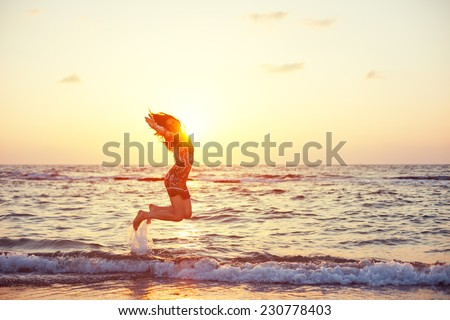 young and beautiful girl in colorful dress jumping in ocean water in sunset - stock photo