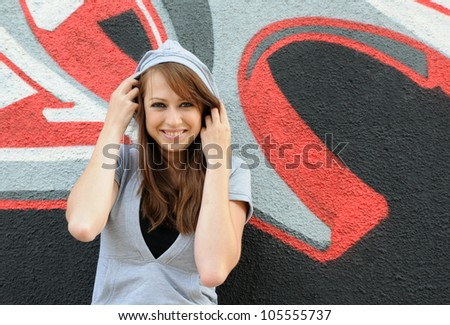 Young and beautiful girl posing against wall with graffiti - stock photo