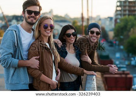 Young and beautiful. Group of young people standing close to each other on the bridge and looking at camera with smiles - stock photo