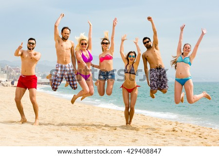 Young and beautiful happy adults jumping on a sandy beach on a seashore on a sunny day - stock photo