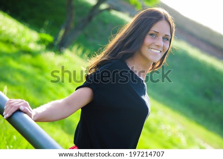 Young and beautiful lady is smiling and enjoying nice weather - stock photo