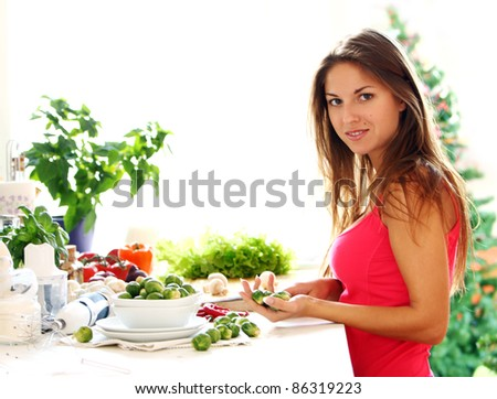 Young and beautiful woman cooking healthy food - stock photo