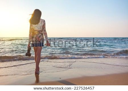 young and beautiful woman in colorful dress standing on the beach near the ocean and looking far away at the sunset - stock photo