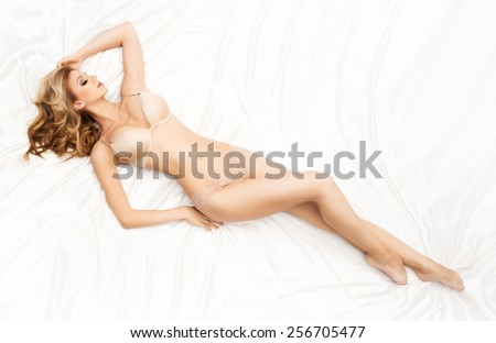 Young and beautiful woman in sexy underwear posing in the bed - stock photo