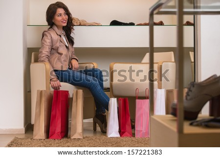 Young and beautiful woman trying on new shoes at store with shopping bags around - stock photo