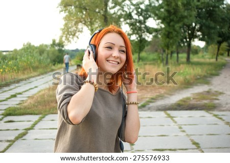 Young and beautiful woman wearing headphones listening to music and singing on the background of nature city park. Woman with headphones listening music. Music teenager girl dancing against.  - stock photo