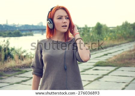 Young and beautiful woman wearing headphones listening to music and singing on the background of nature city park and river. Woman with headphones listening music. Music teenager girl dancing against. - stock photo