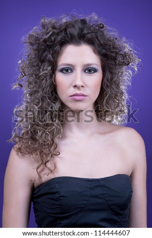 young and beautiful woman, with curly hair, on purple background, side view, studio shot - stock photo