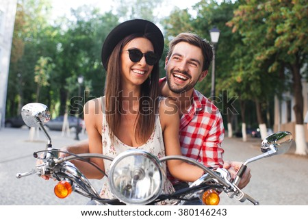 Young and carefree couple learning to drive a scooter on a road. Young man is teaching hipster girl to ride a motorcycle. - stock photo