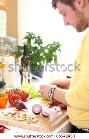 Young and cheerful woman cooking healthly food - stock photo