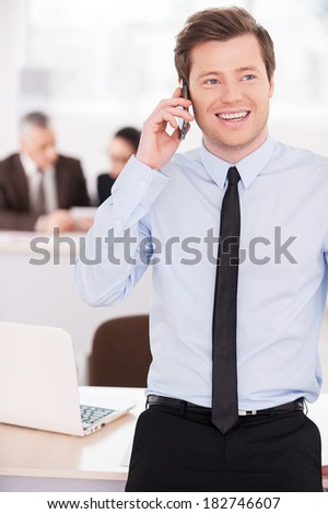 Young and confident team leader. Confident young man in formalwear talking on the mobile phone and smiling while his colleagues working on background - stock photo