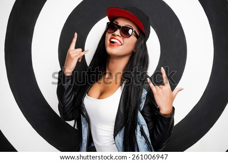 Young and cool. Cheerful young African woman in baseball cap smiling and gesturing while standing against black and white background - stock photo