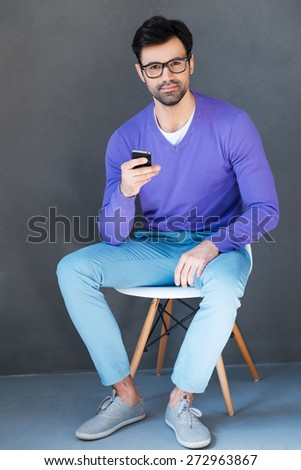 Young and creative. Handsome young man holding mobile phone and looking at camera while sitting against grey background  - stock photo