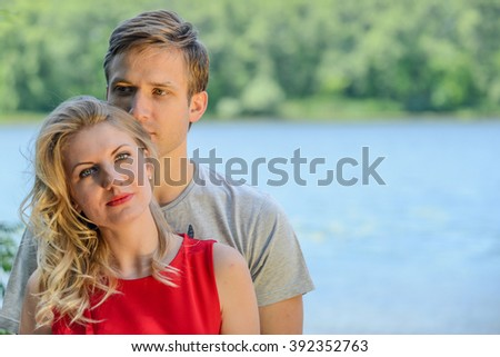 Young and cute happy couple hugging and laughing on river background - stock photo