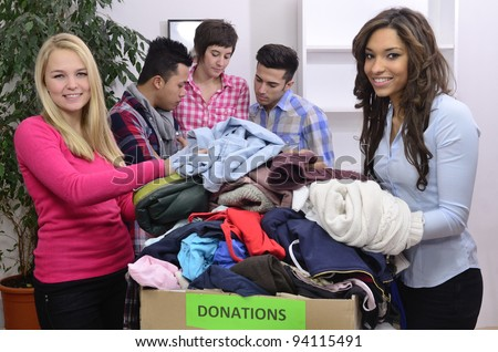 young and diverse volunteer group with clothing donation - stock photo