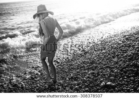 Young and elegant woman in stripped dress with a hat walking to the sea on the beach on sunset. Black and white photo - stock photo