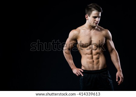 Young and fit male model posing his muscles looking downwards isolated on black background. Man showing his six pack abs on dark background - stock photo