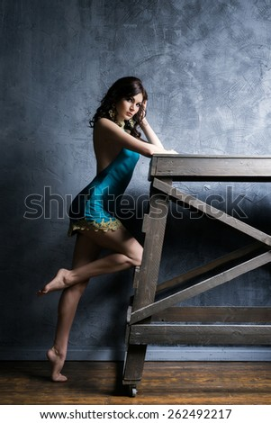 Young and graceful woman posing in a fashion clothes. Ancient and shabby interior. - stock photo