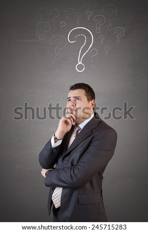 Young and handsome businessman thinking (have no idea) in front of question marks concept - stock photo