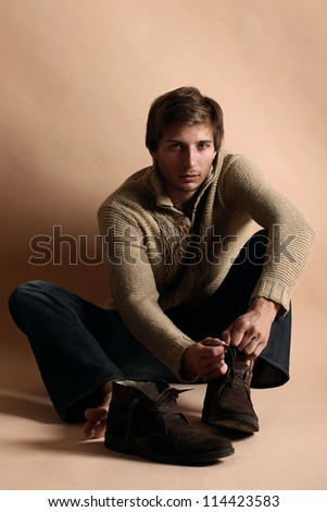 Young and handsome guy lacing a shoes - stock photo