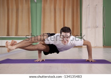 young and handsome male doing yoga - stock photo