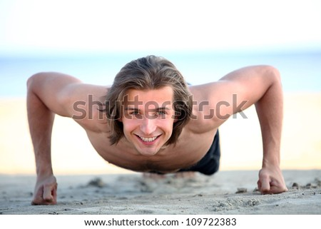 Young and handsome man doing push ups on the beach - stock photo
