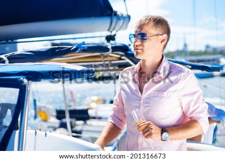 Young and handsome man on a luxury yacht - stock photo
