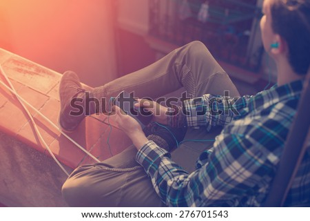 Young and handsome traveler man sitting on the roof and listening music on his mobile phone (intentional sun glare and vintage color, focus on mobile phone) - stock photo