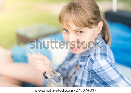 Young and happy blonde girl eating dessert with long spoon outside. Woman looking into camera and smiling. Background blurred and out of focus. - stock photo
