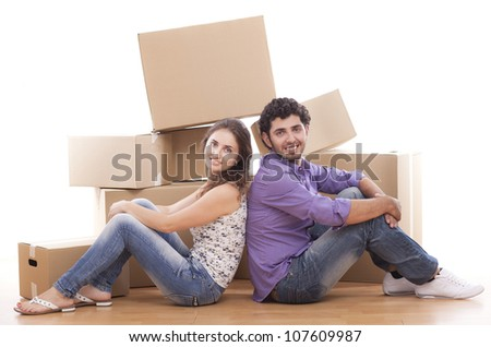 Young and happy couple are carrying boxes to new house - stock photo