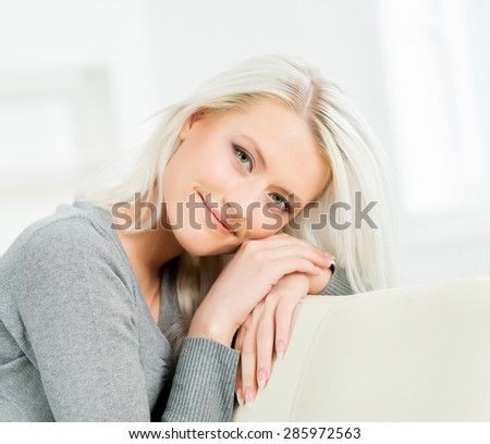 Young and happy woman resting on sofa at home - stock photo