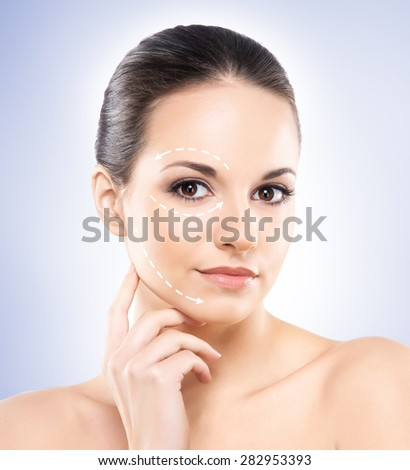 Young and healthy woman with arrows on her face - stock photo