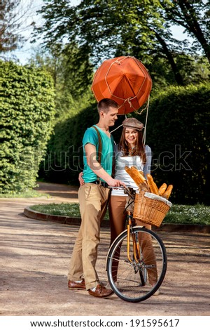 Young and joyful couple having fun in the park with bicycle and airship on it - stock photo