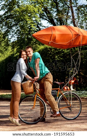 Young and joyful couple hugging in the park with bicycle and airship on it - stock photo
