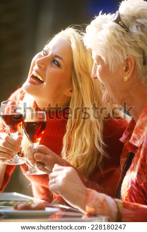 Young and mature woman clinking glasses with red wine - stock photo