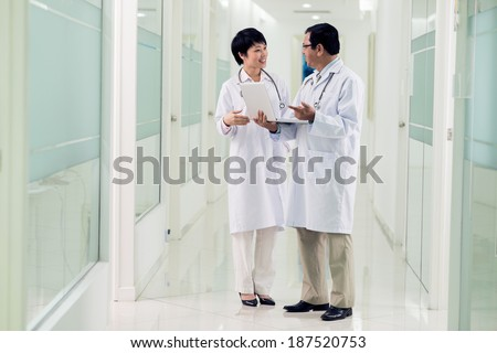 Young and middle-aged doctors speaking in the hospital - stock photo