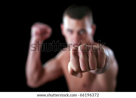 young and muscular boxer is giving his finishing punch in front of black background.Martial art concept - stock photo