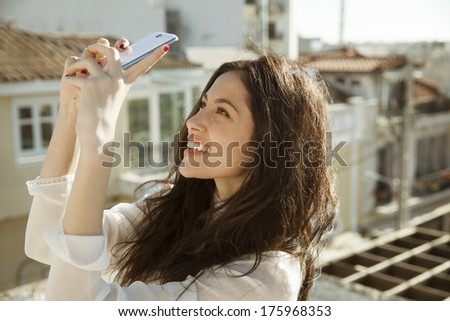 Young and pretty woman taking photo with her phone. outdoors shot. vertical - stock photo