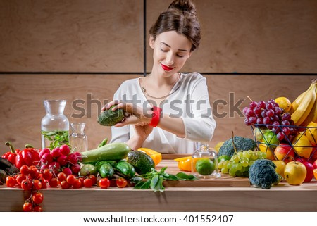 Young and pretty woman watching smart watch sitting at the table full of fruits and vegetables in the wooden interior. Counting calories with smart watch app. Food and health care concept - stock photo