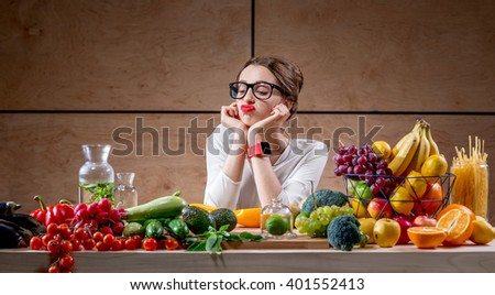 Young and sad woman thinking about tasty food and calories sitting at the table full of fruits and vegetables in the wooden interior. - stock photo