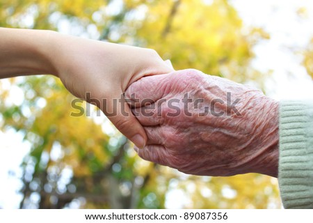 Young and senior holding  hands in autumn - stock photo
