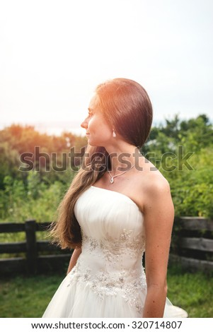 Young and sensual woman looking at camera posing with a wedding dress in the beach - stock photo
