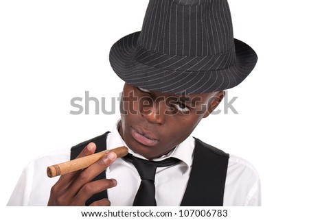 young and sexy black man wearing a hat and smoking a cigar - stock photo