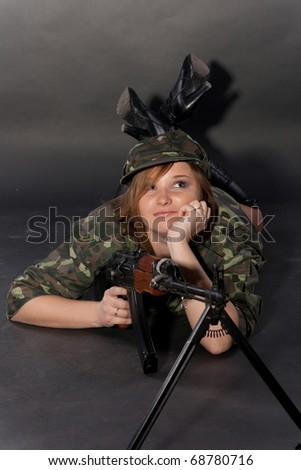 Young and sexy female model in military outfit posing in studio with airsoft AK-series machine gun - stock photo