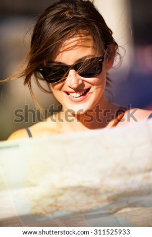 Young and smiling woman portrait consulting a map in the street. Close up. - stock photo
