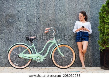 Young and stylish. Beautiful young smiling woman standing near her vintage bicycle on the street  - stock photo