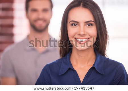 Young and successful. Beautiful young woman looking at camera and smiling while man standing behind her - stock photo